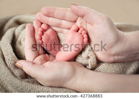 Small feet baby feet holds in mother's hands - stock photo