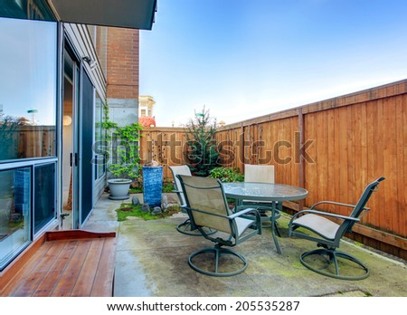 Small fenced backyard with patio table set - stock photo