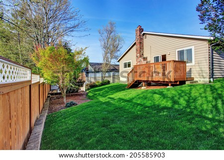 Small fenced backyard with wooden walkout deck - stock photo
