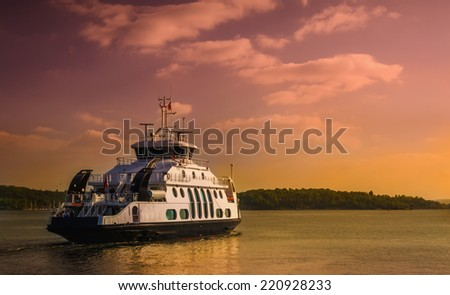 Small ferry cruising on sunset in Oslo fjord, Norway - stock photo