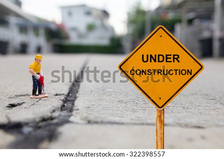 small figure of a man digging concrete street with Under Construction message. - stock photo