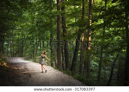 Small figure of young woman dancing on path in green forest with big tall trees illuminated by evening sunshine - stock photo