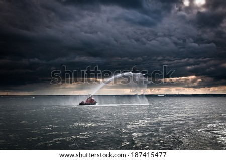 small fireboat demonstrating its capabilities on Baltic Sea in Gdansk, Poland - stock photo