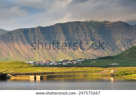 Small fisherman village among mountains near the water in West Iceland on a cloudy summer day - stock photo