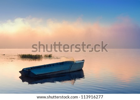 Small fishing boat and large frontal cloud of mist at sunrise - stock photo