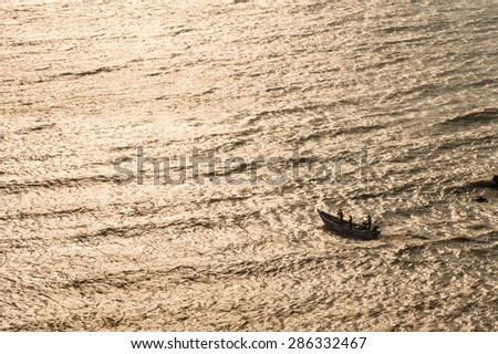 Small fishing boat heads out from the port at Kanyakumari, in south India. - stock photo