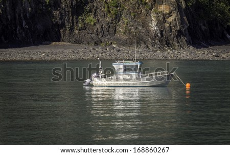 Small fishing boat near harbor in the morning sun - stock photo