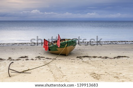Small fishing boat on sandy beach of the Baltic Sea - stock photo