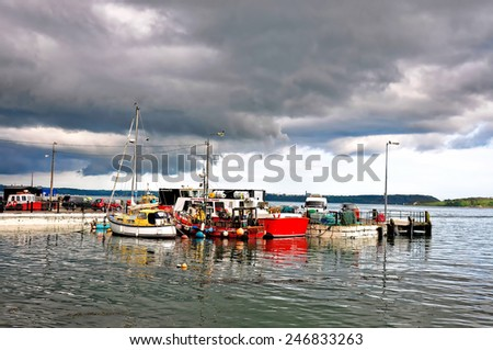 Small fishing boats park at a dock near Cork Harbour in a cloudy day - stock photo