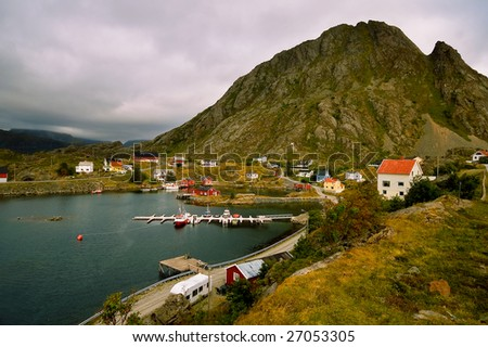 Small fishing village at a base of a high mountain, Lofoten Islands, Norway - stock photo
