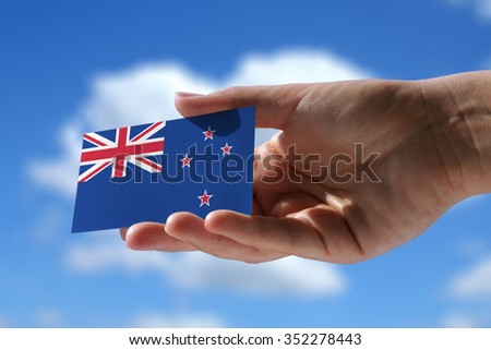 Small flag of New Zeland, cumulus clouds in background - stock photo