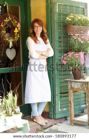 Small florist shop owner standing at facade.  - stock photo