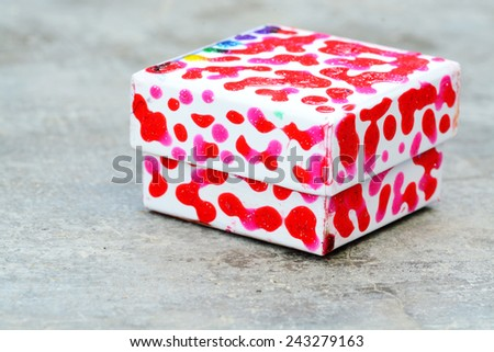 Small gift box made and decorated with paint by a kid on a gray concrete background - stock photo