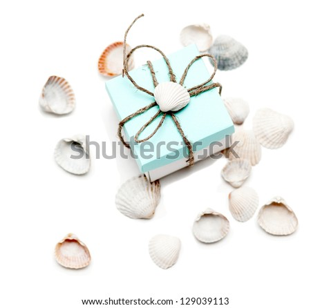 small gift with conchs on white background - stock photo