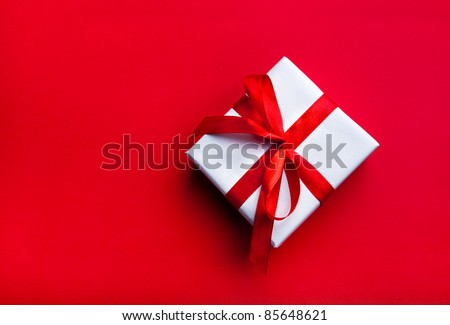 Small gift with red bow on red background. Free space for your text. - stock photo