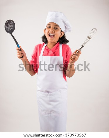 small girl chef, small girl cook, asian small girl in chef uniform, Indian girl in chef attire, cooking and people concept - smiling little girl in cook hat - stock photo