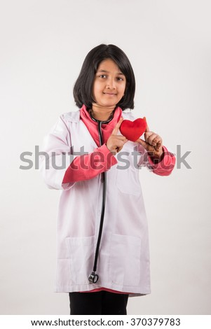 small girl doctor with stuffed heart - stock photo