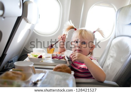 small girl eating in the airplane - stock photo
