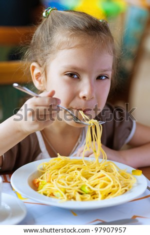 Small girl eating spaghetti with fork and smiles. - stock photo