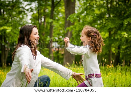 Small girl enjoying life with her mother outdoor in nature - stock photo