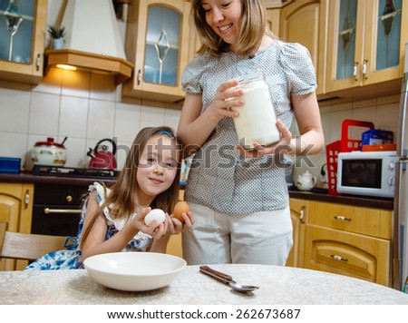 Small girl help her mother making breakfast. Cooking together - stock photo