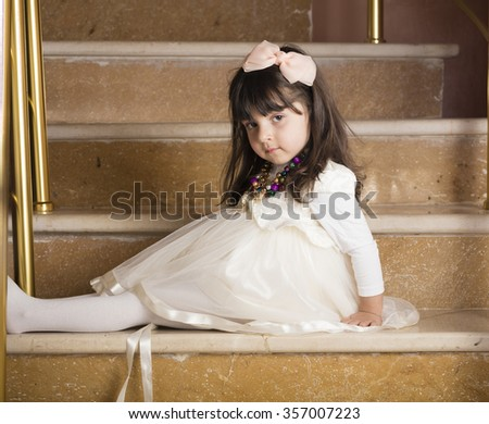small girl in off white bride dress sitting on stairs  - stock photo
