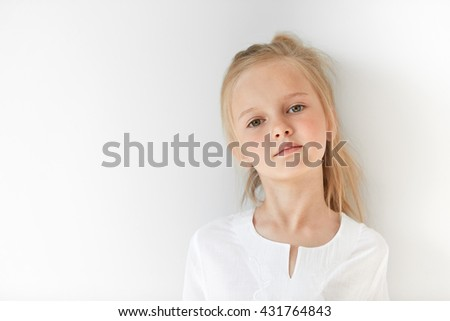 Small girl in white light room looking pretentiously at camera with her chin raised and head tilted. Pride and honor mixed with childish self-assurance and confidence show her superior attitude. - stock photo