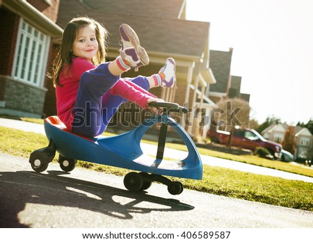small girl is having fun riding his toy on the street - stock photo