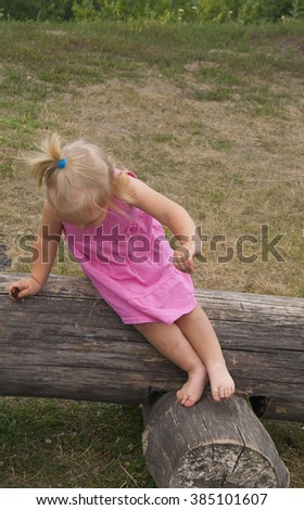 small girl stretching over the log - stock photo