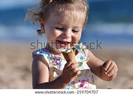 Small girl taking an ice cream in the beach - stock photo