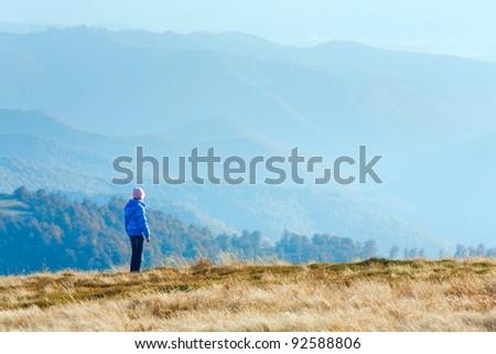 Small girl walk on autumn  mountain plateau. - stock photo
