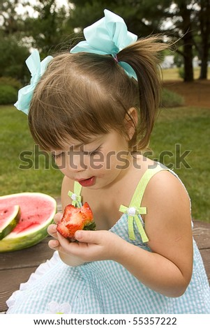 Small girl wearing sundress eating strawberries and watermelon - stock photo