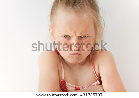 Small girl with blond pony-tail looking seriously, folding hands and frowning eyebrows. Her gloomy appearance says she is very unhappy and offended. Blond baby showing disapproval with pursed lips. - stock photo