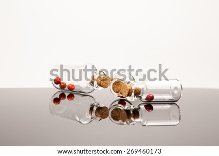 Small glass bottles with red pepper and reflexions - stock photo