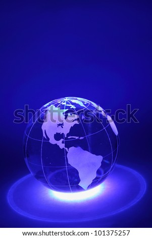 Small glass globe is illuminated by blue light from below; North and South America - stock photo