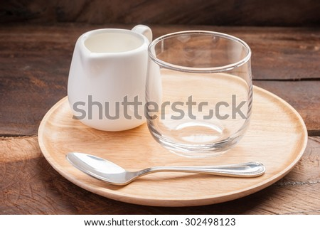 small glass jar and teaspoon on wooden plate background - stock photo