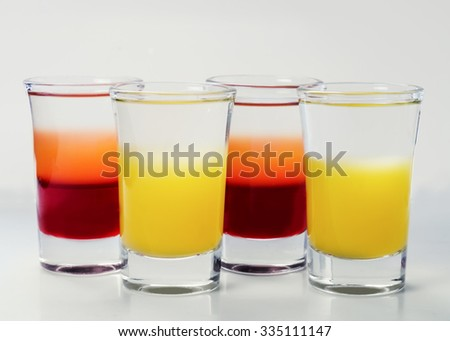 small glass shot glasses with alcohol on a white background. - stock photo