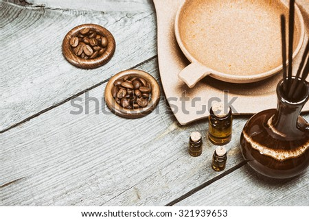 Small glass vials filled with natural aromatic essential oils next to crock with incense sticks, bamboo utensil with water and coffee beans on old wooden planks. Toned image in retro style. Copy space - stock photo