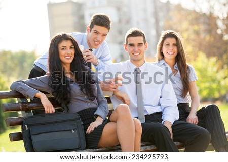 Small group of business people, elegantly dressed, on a coffee break in the park, sitting on a bench, enjoying the beautiful weather and with a smile on their faces looking at the camera. - stock photo