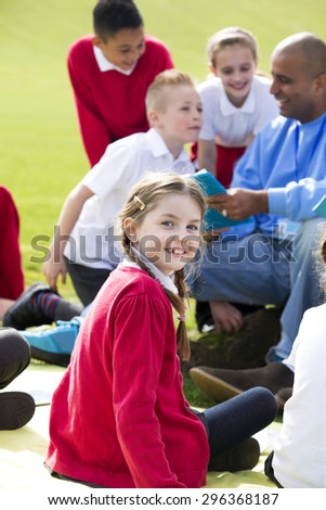Small group of children sitting on the grass having a lesson outdoors. Male teachers can be seen. The children look to be listening and enjoying themselves. One little girl smiles at the camera. - stock photo