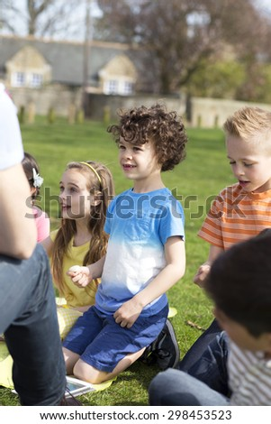Small group of children sitting on the grass having a lesson outdoors. Only side of the teacher can be seen. The children look to be listening.  - stock photo