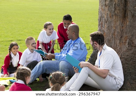 Small group of children sitting on the grass having a lesson outdoors. Two male teachers can be seen. The children look to be listening and enjoying themselves.  - stock photo
