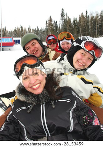 Small group of  snowboarders laying on slope, smiling. - stock photo