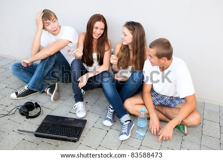 small group of students sitting on street - stock photo