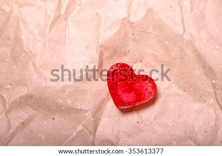 Small heart from translucent red ice on the crumpled packing paper of light-beige color. Such paper is used for packing of various goods - stock photo