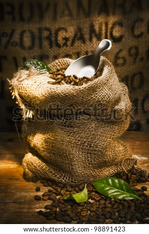 Small hessian sack filled with fresh roasted coffee beans topped by a small shovel with the word Organic highlighted on hessian in the background, conceptual of organically grown coffee - stock photo