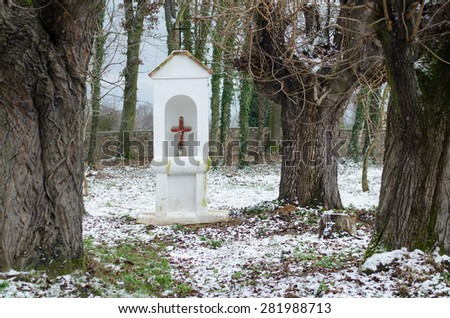Small historic shrine between the old trees - stock photo