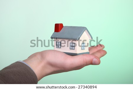 Small house in a hand on a green background - stock photo