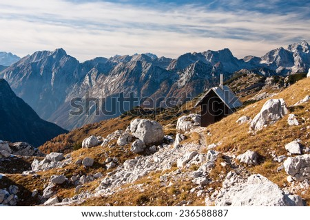 Small house in the mountains in Triglav national park in autumn lighted by afternoon sun, Slovenia - stock photo