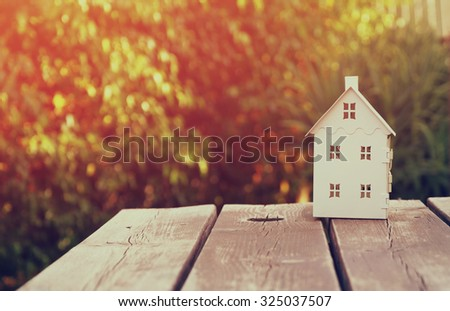 small house model over wooden table outdoors at garden . filtered image. selective focus - stock photo